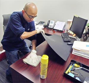 Miguel Moreno polishes a desk at Royal Business Bank in San Gabriel Thursday Oct. 29, 2009.